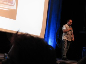 Dirk Bartholomä auf der Bühne neben dem Projektionsschirm.