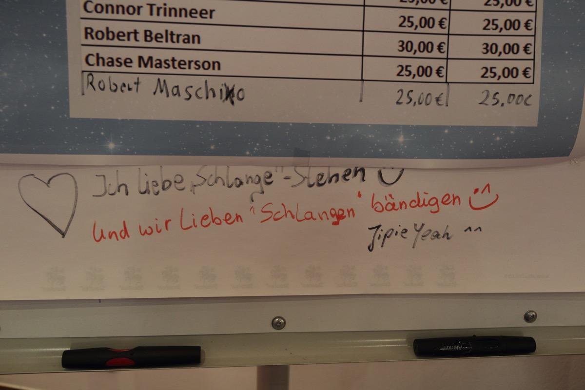 Handschrift, Ich liebe es, Schlange zu stehen. :-) Darunter in anderer Handschrift: Und wir lieben es, Schlangen zu bändigen, Yippiejayeah!