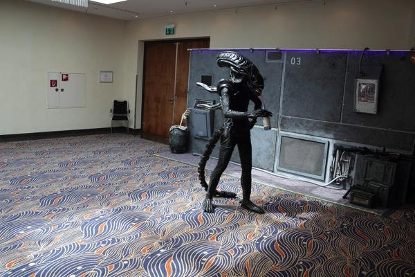 Ein Alien im Vollkostüm, also auch mit Helm und so, trinkt mit Strohhalm aus Flasche